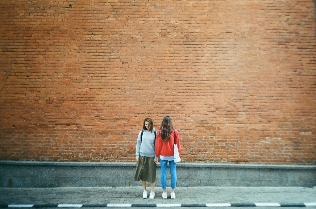 two-women-standing-beside-red-brick-wall-2708912